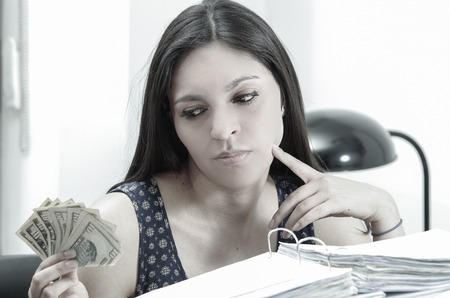 ultrabook: Hispanic brunette office woman sitting by desk with paper files archive open and holding several ten dollar bills.
