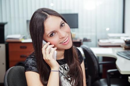 executive women: Hispanic brunette sitting by office desk talking on telephone smiling with positive attitude. Stock Photo