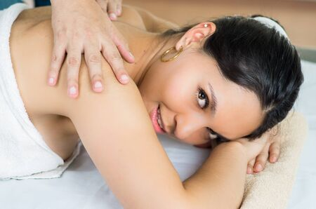 masajes relajacion: Hispanic brunette model getting massage spa treatment, white towel covering upper body lying horizontal smiling to camera with hands working on shoulders. Foto de archivo
