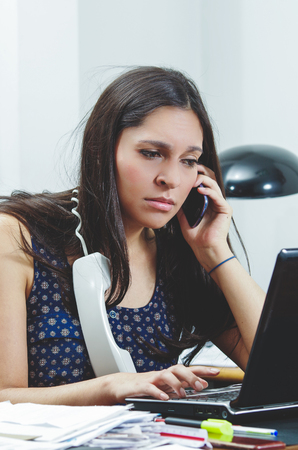 occupied: Hispanic brunette sitting by office desk talking on telephone with occupied and worried facial expression.