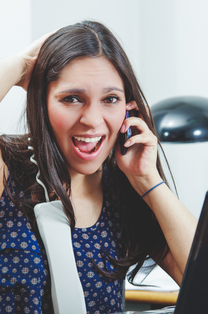 ultrabook: Hispanic brunette sitting by office desk talking on telephone with occupied and worried facial expression.
