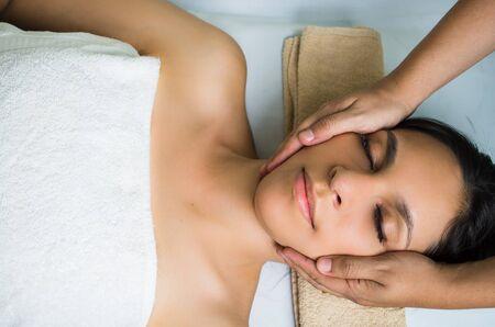 masajes relajacion: modelo morena hispana recibiendo tratamiento de spa masaje, masaje de manos que trabajan en la mujer cabeza y la cara con los ojos cerrados. Foto de archivo