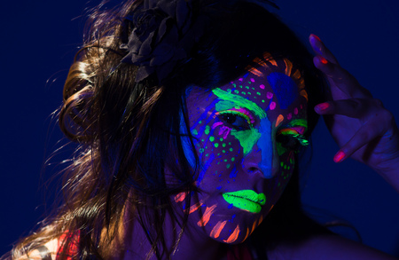 facing on camera: Headshot woman wearing awesome glow in dark facial paint, blue based with other neon colors and obscure abstract background, facing camera. Stock Photo