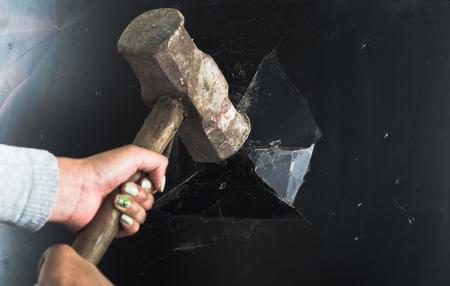 Closeup large metal hammer smashing black computer screen.