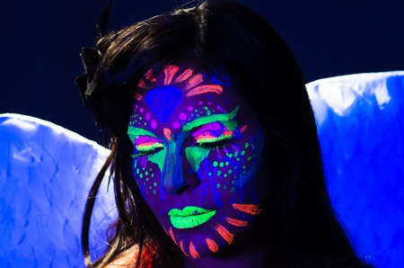 obscure: Headshot woman wearing awesome glow in dark facial paint, blue based with other neon colors and obscure abstract background, facing camera. Stock Photo