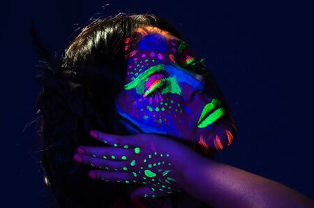 facing to camera: Headshot woman wearing awesome glow in dark facial paint, blue based with other neon colors and obscure abstract background, facing camera. Stock Photo
