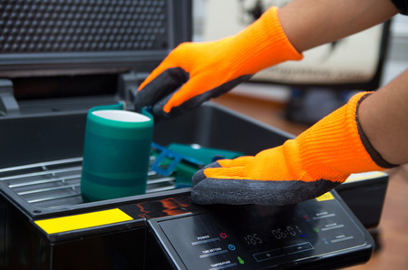 silk screen: Hands wearing orange gloves working on black print screen machine.