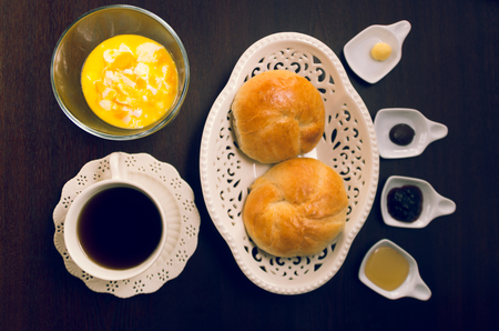 marmelade: Cup of tea, hot water decanter and nice white bowl with two beautiful breads inside, marmelade selection.