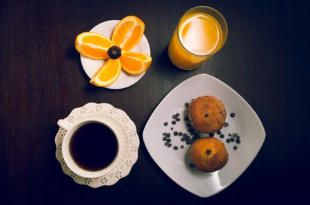 choc: Elegant breakfast concept seen from above, coffee cup, choc chip muffin, orange juice and sliced oranges.
