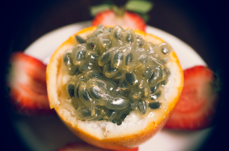 grenadilla: Closeup open grenadilla with sliced strawberries laying around on white plate. Stock Photo