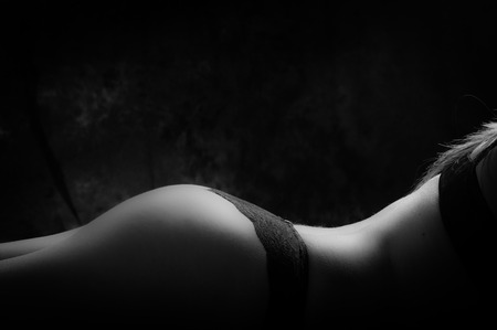 naked girl black hair: Artistic caption of attractive womans butt wearing sexy panties, lying horizontally, black and white edition.