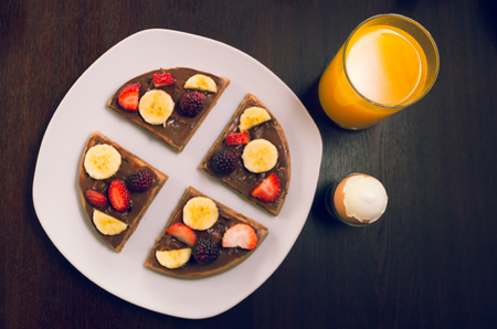 cereal bar: Pancake cut in four parts decorated with fruits, glass of orange juice and a boiled egg. Stock Photo