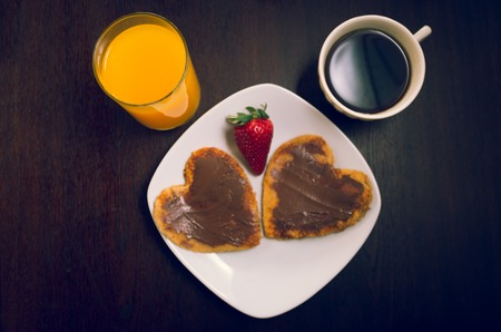 cofee cup: Heartshaped pancakes covered with chocolate and strawberry, orange juice, cofee cup as seen from above, elegant breakfast concept.