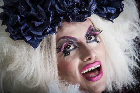 trashy: Drag queen with spectacular makeup, glamorous trashy look, posing happily and charming camera from sideways angle.