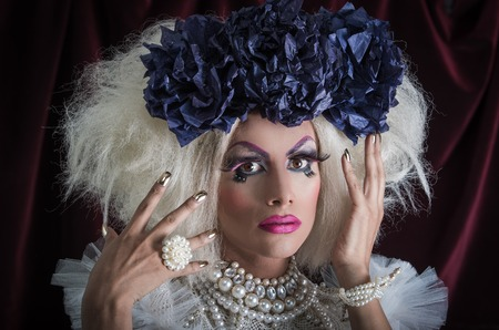 trashy: Drag queen with spectacular makeup, glamorous trashy look, posing while using hands and fingers.