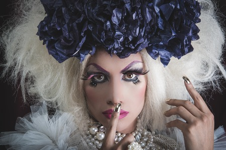 Drag queen with spectacular makeup, glamorous trashy look, posing while using hands and fingers.