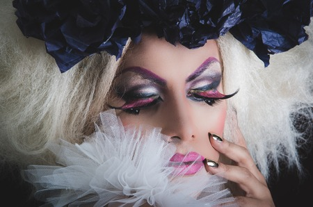 drag queen: Drag queen with spectacular makeup, glamorous trashy look, posing happily and charming camera from sideways angle.