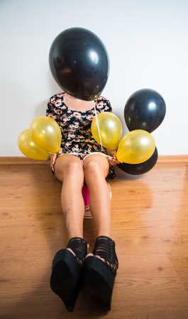 face covered: Model wearing summer dress sitting on wooden floor holding black and golden balloons, face covered by balloon.