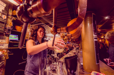 delirium: BRUSSELS, BELGIUM - 11 AUGUST, 2015: Bartender at Delirium Bar tapping beer into tall glass with several other taps next to it.
