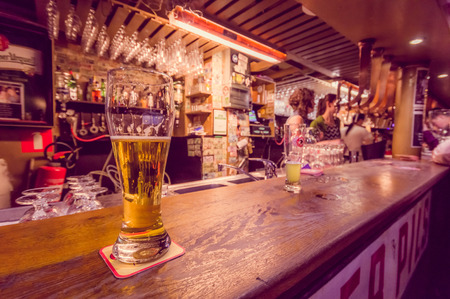 delirium: BRUSSELS, BELGIUM - 11 AUGUST, 2015: Glass of beer sitting on bar counter inside Delirium Bar, selection of other beverages in background. Editorial
