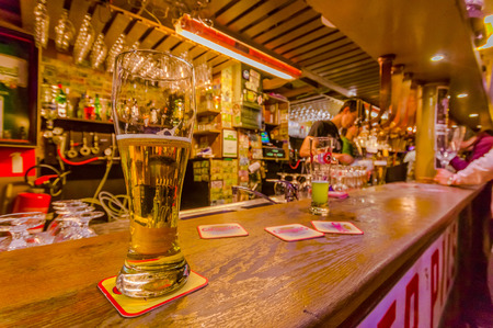 BRUSSELS, BELGIUM - 11 AUGUST, 2015: Glass of beer sitting on bar counter inside Delirium Bar, selection of other beverages in background. Editorial