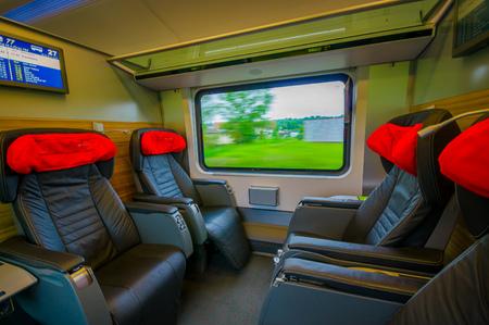baranda para balcon: Vienna, Austria - 11 August, 2015: Inside business class seating area on the train,  large black leather seats.