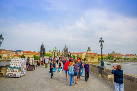 alongside: Prague, Czech Republic - 13 August, 2015: People crossing over famous Charles Bridge, statues visible alongside.