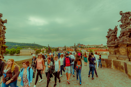 alongside: Prague, Czech Republic - 13 August, 2015: People crossing over famous Charles Bridge, statues visible alongside,