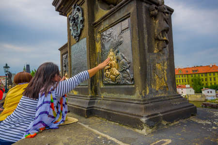 famous statues: Prague, Czech Republic - 13 August, 2015: Charles Bridge and one of its many famous statues, as per tradition people touch them.