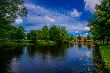Harlem, Amsterdam, Netherlands - July 14, 2015: Beautiful small lake sorrounded by green park environment and traditional brick houses in distance.