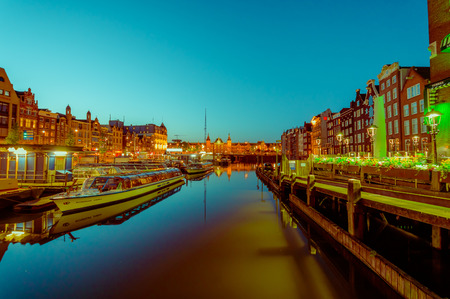 Amsterdam, Netherlands - July 10, 2015: Water channels by night, beautiful dark blue sky and city lights on both sides.