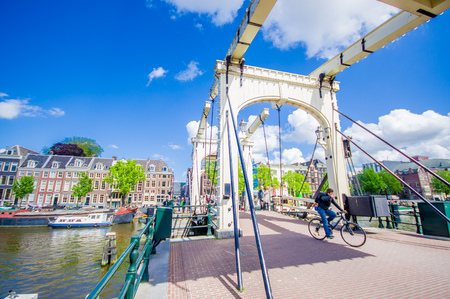 Amsterdam, Netherlands - July 10, 2015: Old metal bridge with beautiful design, stretching across one of many water channels. Editorial