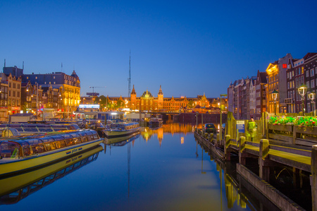 nice accommodations: Amsterdam, Netherlands - July 10, 2015: Water channels by night, beautiful dark blue sky and city lights on both sides.