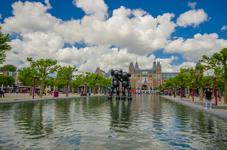 nice accommodations: Amsterdam, Netherlands - July 10, 2015: Large water fountain located in front of the National Museum on a beautiful sunny day.