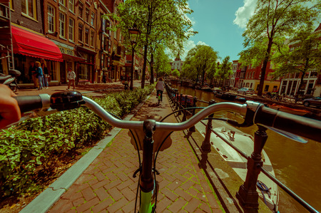 nice accommodations: Amsterdam, Netherlands - July 10, 2015: Bikers point of view as bicycling through city streets, beautiful sumer day with water channel on right side.