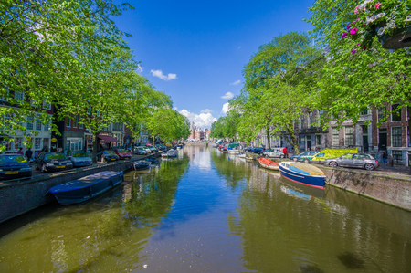 nice accommodations: Amsterdam, Netherlands - July 10, 2015: Water channel seen from small bridge, green trees and residencial buildings alongside.