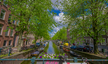 residencial: Amsterdam, Netherlands - July 10, 2015: Water channel seen from small bridge, green trees and residencial buildings alongside.
