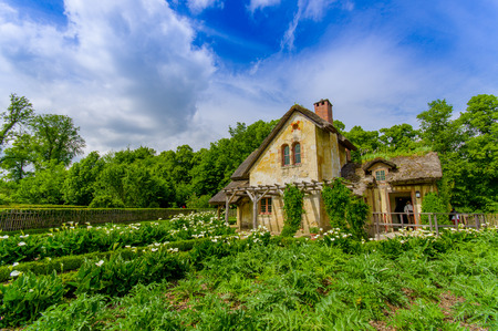 Paris, France - June 1, 2015: The Queens Hamlet, Versailles, built as a leisure retreat for her majesty and closest friends, beautiful rustic architecture with lakes, garden environment.