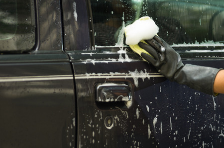 soapy water: Closeup black rubber gloves working on washing car door window with soapy water.