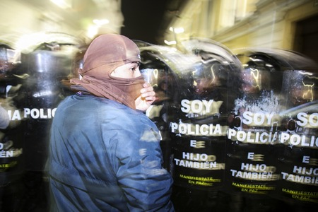 occupy movement: Quito, Ecuador - August 27, 2015: Man wearing denim jacket and face covered standing in front of police shields protesting.
