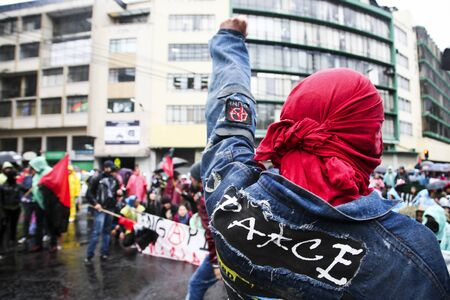 lega: Quito, Ecuador - August 27, 2015: Man wearing denim jacket with peace patch on back raising fist towards crowd of people in city streets.