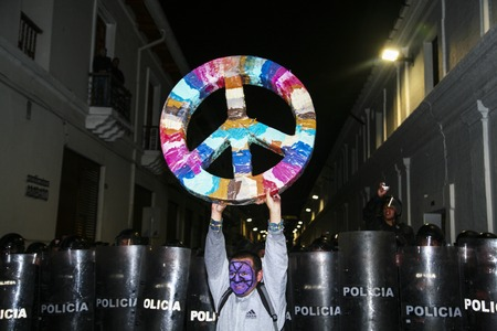 occupy movement: Quito, Ecuador - August 27, 2015: Man wearing facial paint holding large peace symbol in front of lined up riot police Quito city streets. Editorial