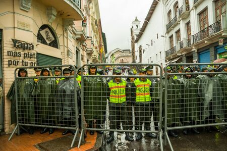 demonstrations: Quito, Ecuador - August 27, 2015: Policemen behind metal fence barrricade awaiting orders during mass demonstrations.