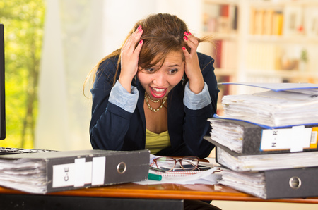 bent over: Business woman sitting by desk, paper files spread out, elbows on table and head bent over as expressing great frustration.