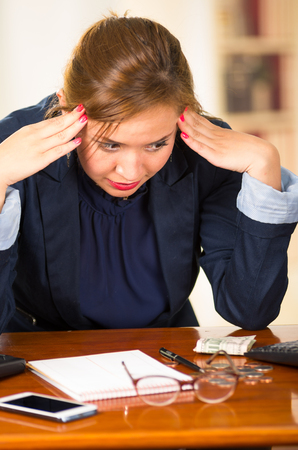 bent over: Business woman sitting by desk, elbows on table and head bent over as expressing great frustration.