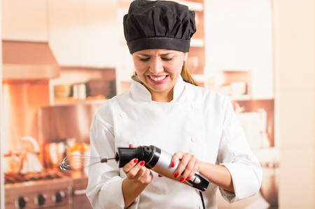 unsatisfied: Woman chef holding a broken electric blender with unsatisfied facial expression.