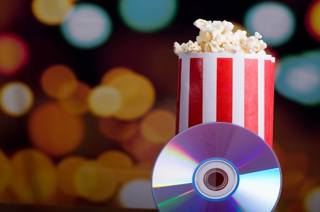 Closeup red white striped container standing up with popcorn reaching over edge, dvd disc leaning on box, low angle, flashy vivid lights background.
