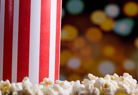 flashy: Closeup red white striped container box standing up with popcorn lying around, low angle, flashy vivid lights background. Stock Photo