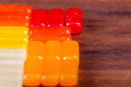 hard candy: Closeup colorful rectangular hard candy lying on wooden surface.