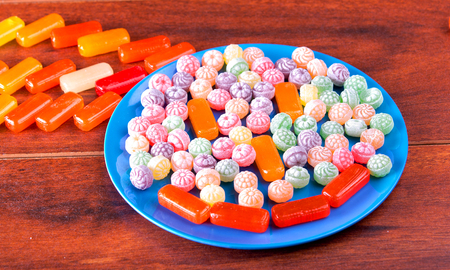 hard candy: Variation of colorful hard candy lying on blue plate.